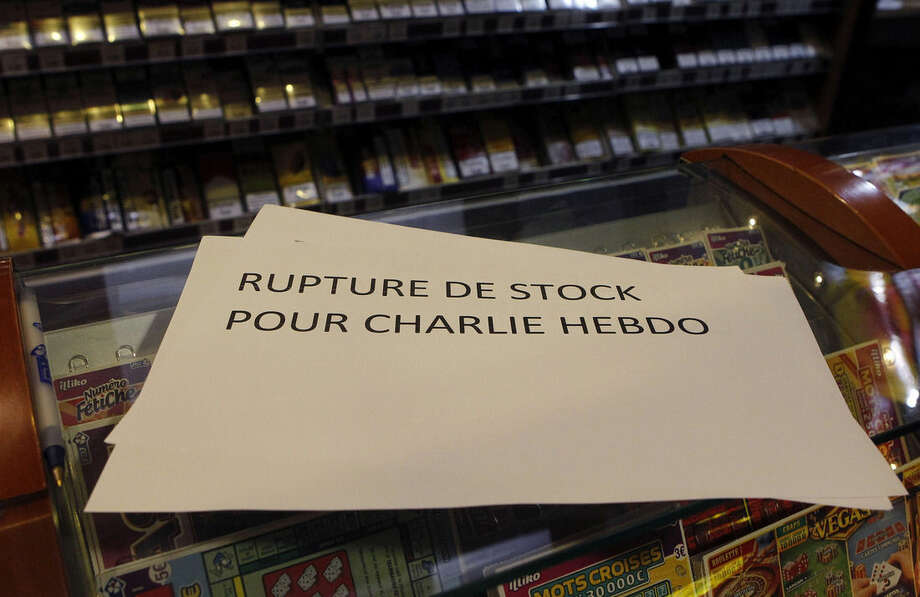 """A banner reading: """" Stock shortage for Charlie Hebdo"""" is placed at a newsstand in Lille, northern France, Wednesday, Jan. 14, 2015. In an emotional act of defiance, Charlie Hebdo resurrected its irreverent and often provocative newspaper, featuring a caricature of the Prophet Muhammad on the cover that drew immediate criticism and threats of more violence. (AP Photo/Michel Spingler)"""