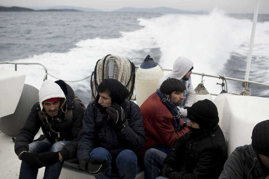 In this photo taken on Wednesday, Jan. 20, 2016, Syrian refugees sit on a Greek Coast Guard vessel during a rescue operation near the Greek island of Chios. Already in 2016, more than 35,000 people have reached Greece by sea despite plunging winter temperatures and days of stormy weather. Hour after hour, by night and by day, Greek coast guard patrol and lifeboats, reinforced by vessels from the European Union's border agency Frontex, ply the waters of the eastern Aegean Sea along the frontier with Turkey, on the lookout for people being smuggled onto the shores of Greek islands - the frontline of Europe's massive refugee crisis. (AP Photo/Petros Giannakouris)