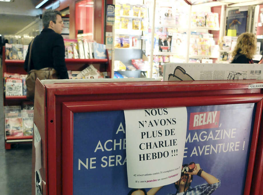 "People browse a newsstand advertising ""We don't have any more Charlie Hebdo"" in Paris, France, Wednesday, Jan. 14, 2015. Charlie Hebdo's defiant new issue sold out before dawn around Paris on Wednesday, with scuffles at kiosks over dwindling copies of the paper fronting the Prophet Muhammad. (AP Photo/Bertrand Combaldieu)"