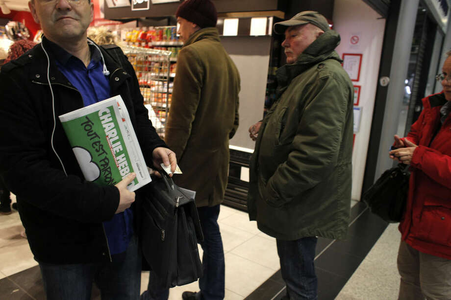 "A man leaves after buying the latest issue of Charlie Hebdo newspaper as people queue up at a newsstand in Paris, Wednesday, Jan. 14, 2015. In an emotional act of defiance, Charlie Hebdo resurrected its irreverent and often provocative newspaper, featuring a caricature of the Prophet Muhammad on the cover that drew immediate criticism and threats of more violence. The black letters on the front page reads: ""All is forgiven."" (AP Photo/Christophe Ena)"