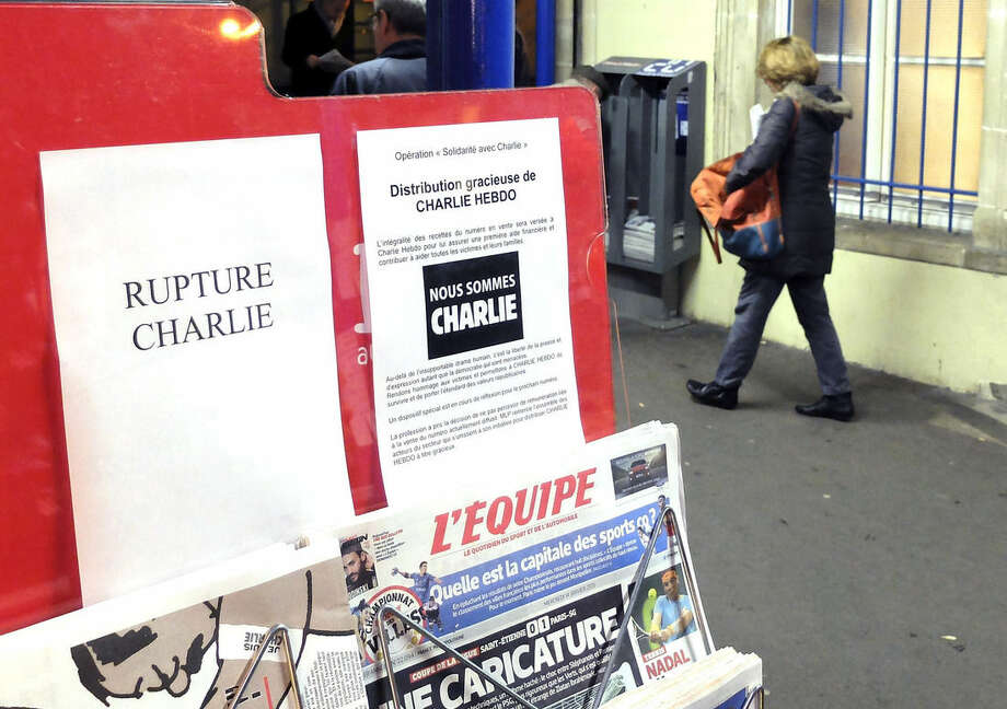 "A woman walks past a newsstand with a sign stating ""Charlie Hebdo sold out"" at the Ville d'Avray train station, west of Paris, France, Wednesday, Jan. 14, 2015. Charlie Hebdo's defiant new issue sold out before dawn around Paris on Wednesday, with scuffles at kiosks over dwindling copies of the paper fronting the Prophet Muhammad. (AP Photo/Bertrand Combaldieu)"