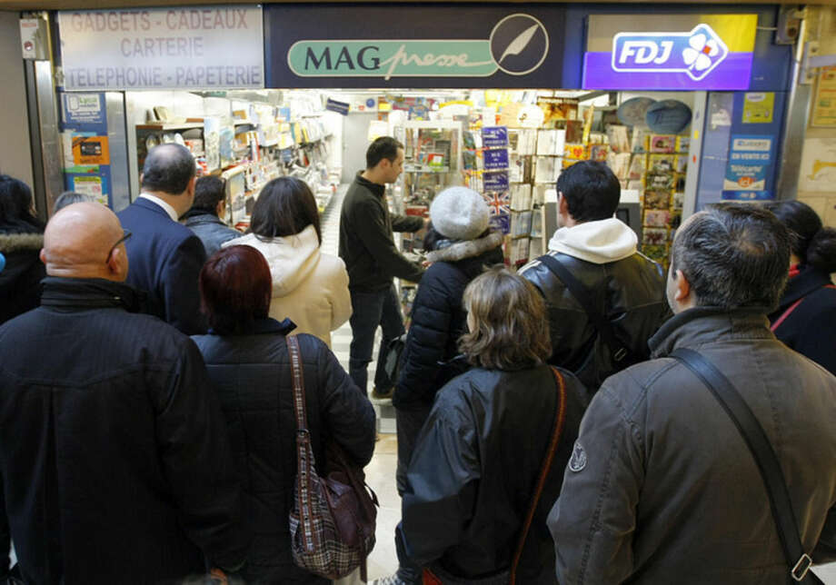 "People wait the opening of a newsstand to buy a copies of satirical newspaper ""Charlie Hebdo"", in Marseille, southern France, Wednesday, Jan. 14, 2015. In an emotional act of defiance, Charlie Hebdo resurrected its irreverent and often provocative newspaper, featuring a caricature of the Prophet Muhammad on the cover that drew immediate criticism and threats of more violence. (AP Photo/Claude Paris)"