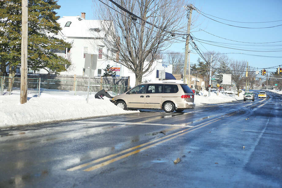 A man trys to free a minivan that got stuck in the snow on East Avenue in Norwalk after Winter Storm Jonas Sunday morning. Hour Photo / Danielle Calloway