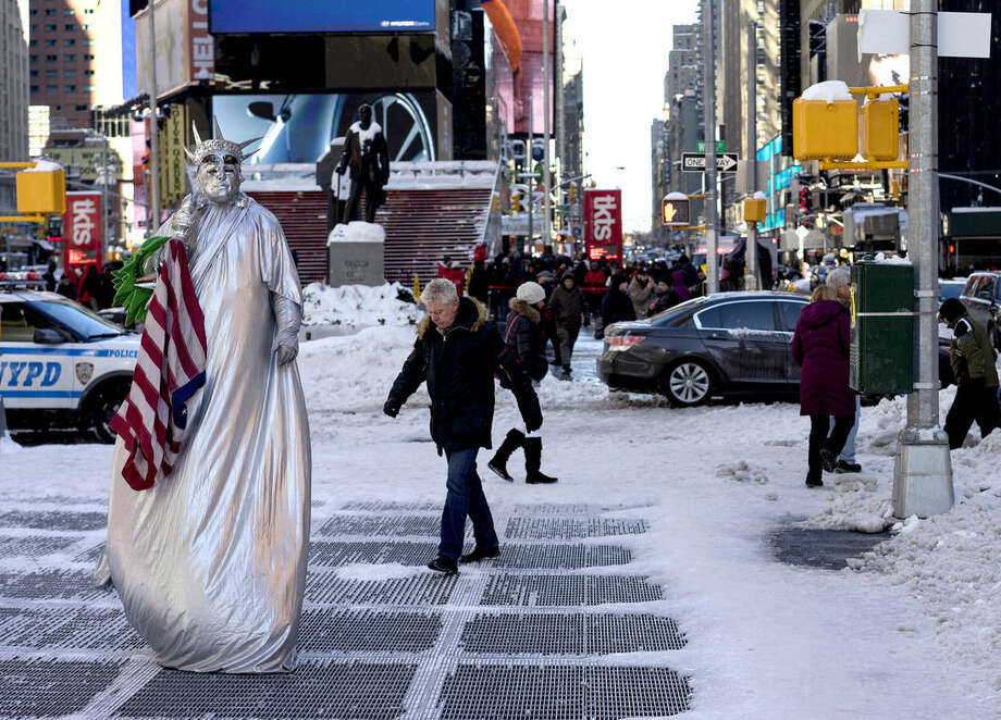 A costumed character, along with pedestrians, navigate sometimes slippery conditions in New York's Times Square Sunday, Jan. 24, 2016, in the wake of a storm that dumped heavy snow along the East Coast. (AP Photo/Craig Ruttle)