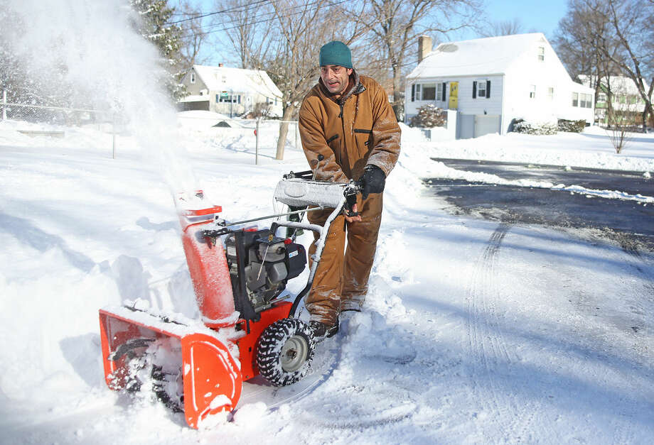 Patrick Robinson uses his snow blower on Rockmeadow Road in Norwalk after Winter Storm Jonas Sunday morning. Hour Photo / Danielle Calloway