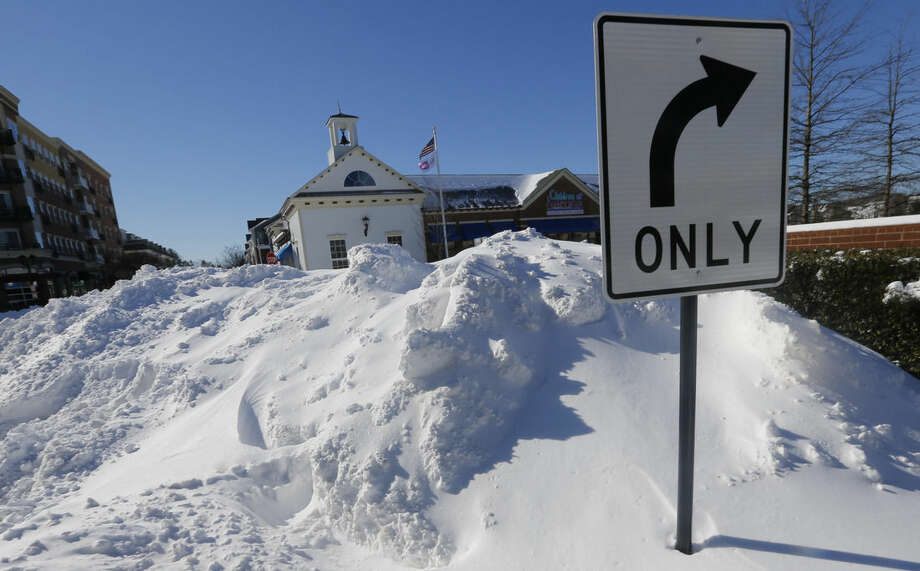 A mound of snow nearly blocks an intersection at a shopping center as area residents dig out from a mammoth snowstorm in Richmond, Va., Sunday, Jan. 24, 2016. (AP Photo/Steve Helber)