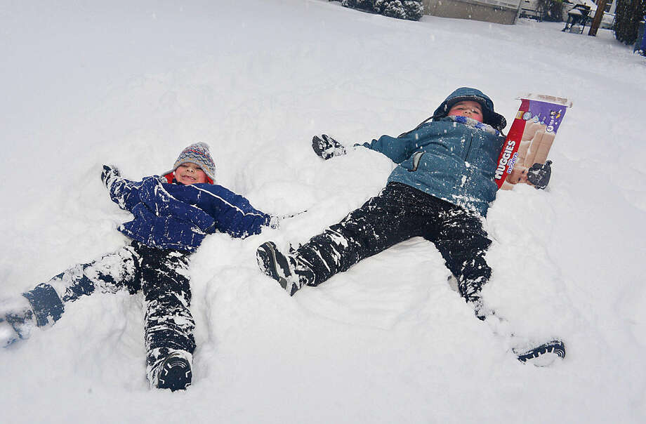 Hour photo / Erik Trautmann Brothers Alex and David Mandujano make snow angels on their front lawn during Snowstorm Jonas on Saturday afternoon.