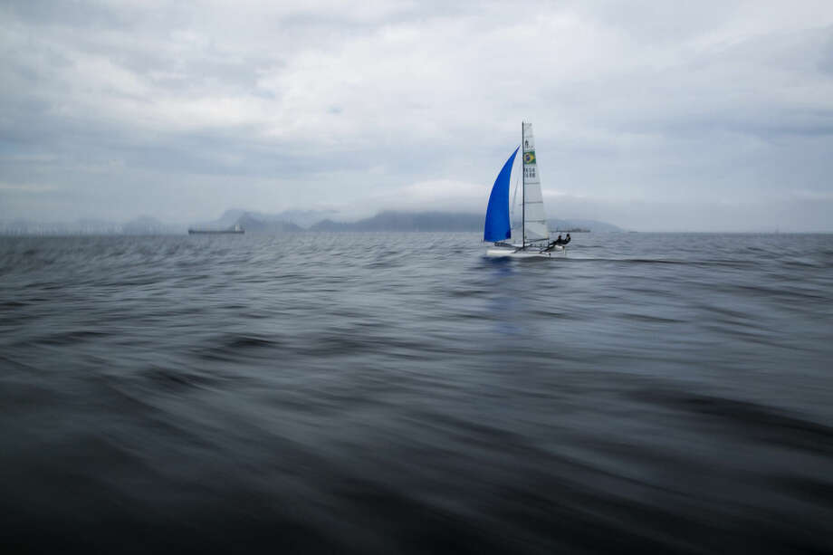 FILE - In this Nov. 3, 2015 file photo, Brazilian athletes Samuel Albrecht and Isabel Swan practice in Guanabara Bay in Rio de Janeiro, Brazil. Independent testing of Guanabara Bay conducted by AP over the last year shows disease-causing viruses linked to human sewage at levels thousands of times above what would be considered alarming in the U.S. or Europe. The tests include the venue for sailing, but also Rio's Olympic venues for rowing, canoeing, open-water swimming and triathlon. (AP Photo/Felipe Dana, File)