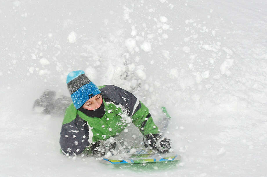 Hour photo / Erik Trautmann Norwalk resident Christopher Dauser sleds at Wolfpit Elementary School during Snowstorm Jonas on Saturday afternoon.