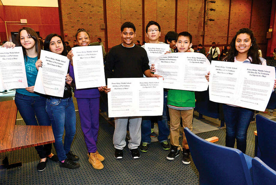 "Hour photo / Erik Trautmann Ponus Ridge Middle School students Breana Montero, Brianna Samaniego, Amanda Clarkhorne, Elijah Jennings, Dyago Cordero, Aldo Salazar and Katerin Hernandez disply their class's signed ""100 Days of No Violence"" agreement Thursday where students pledge to live peacefully over the next 100 days."