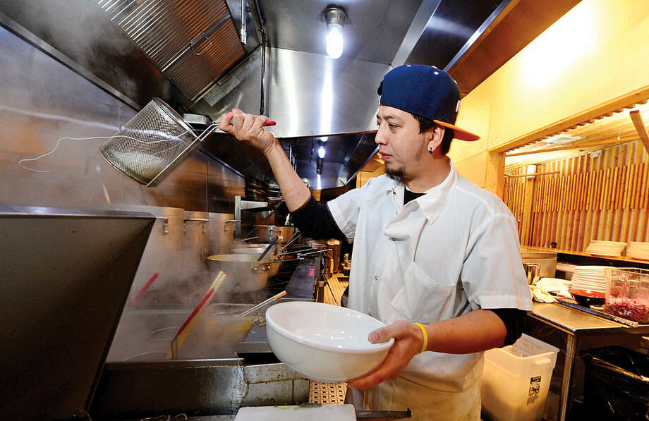 Hour photo / Erik Trautmann Chef Wilfredo Hernandez cooks up rice noodles at the new Mecha Noodle Bar restaurant in SoNo.