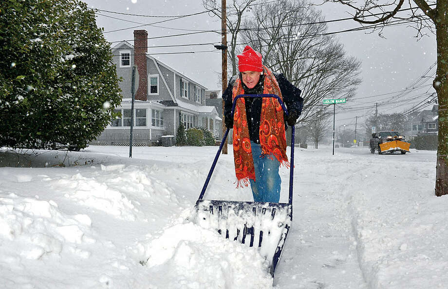 Hour photo / Erik Trautmann Norwalk resident David Siever shovels the walk in front of his home on Ludlowe Manor as Snowstorm Jonas moves through the area Saturday.