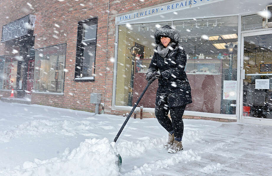 Hour photo / Erik Trautmann Priscilla Yoshida shovels the walk along Wall St as Snowstorm Jonas moves through the area Saturday.