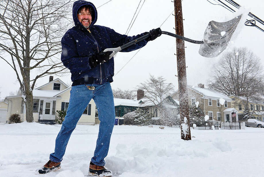 Hour photo / Erik Trautmann Norwalk resident John Yepes shovels the walk in front of his home on Ohio Ave as Snowstorm Jonas moves through the area Saturday.