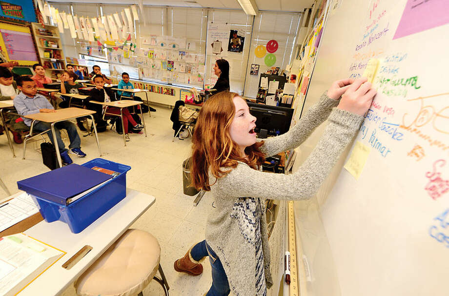 "Hour photo / Erik Trautmann West Rocks Middle School 6th grader Katie Morris affixes a pledge card to the board of Marla Valente's class Thursday as part of the school's ""100 Days of No Violence"" agreement where students pledge to live peacefully over the next 100 days."