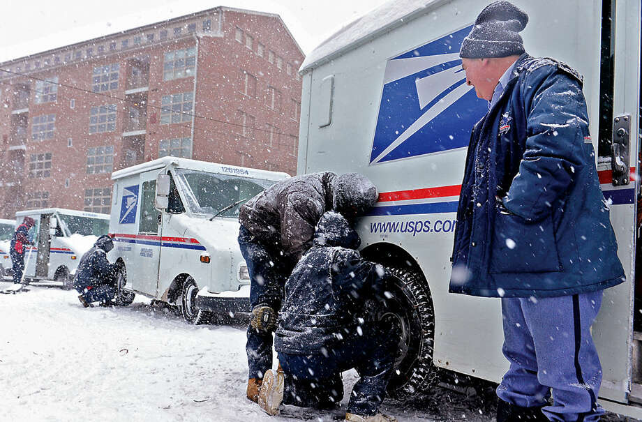 Hour photo / Erik Trautmann Postal carrier Wayne Zola waits for his tires to be chained at Currie Tires as Snowstorm Jonas moves through the area Saturday.