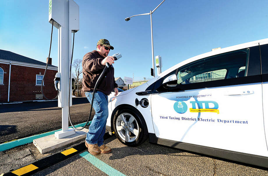 Hour photo / Erik Trautmann Mike Adams, General Line Forman for the Third Taxing District uses the new electric vehicle chargers the District installed at East Norwalk Library on Van Zant Street.
