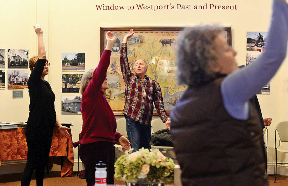 Hour photo / Erik Trautmann Participants follow the instruction of Susan Gold, executive director of the Westport Historical Society, as she leads a thirty-minute class in Qi Gong at the Historical Society Wednesday afternoon.