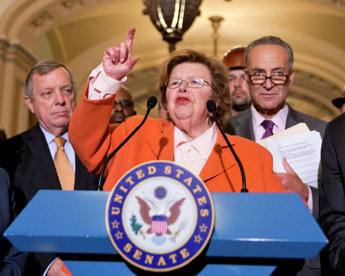 FILE - This Aug. 1, 2013, file photo shows Senate Appropriations Committee Chair Sen. Barbara Mikulski, D-Md., flanked by Senate Majority Whip Richard Durbin of Ill., left, and Sen. Charles Schumer, D-N.Y., speaking on Capitol Hill in Washington. Top congressional negotiators released on Jan. 13, 2014, a bipartisan $1.1 trillion spending bill that would pay for the operations of government through October and finally put to rest the bitter budget battles of last year. The 1,582-page bill was released after weeks of negotiations between House Appropriations Committee Chairman Harold Rogers, R-Ky., and Senate counterpart Mikulski, who kept a tight lid on the details. (AP Photo/J. Scott Applewhite, File)