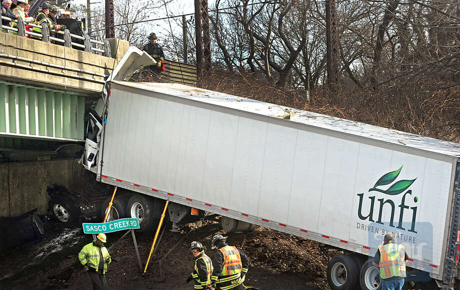 Hour photo / Erik Trautmann Emergency personnel try to free a tractor trailer after in went off the roadway and crashed into the bridge abutment on I-95 Northbound near exit 19 Friday.
