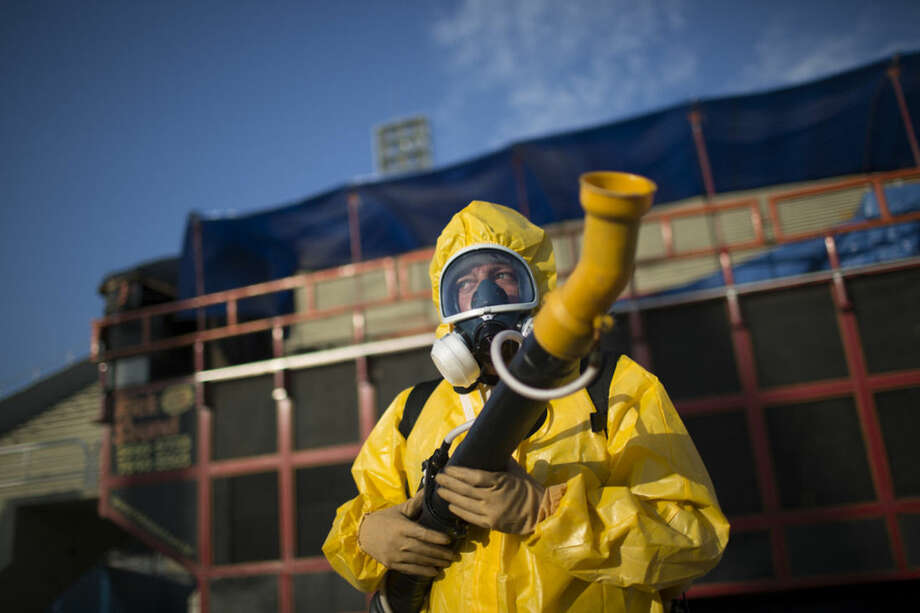 A health worker stands in the Sambadrome as he sprays insecticide to combat the Aedes aegypti mosquitoes that transmit the Zika virus, in Rio de Janeiro, Brazil, Tuesday, Jan. 26, 2016. Inspectors began to spray insecticide around the Sambadrome, the outdoor grounds where thousands of dancers and musicians will parade during the city's Feb. 5-10 Carnival celebrations. Brazil's health minister says the country will mobilize some 220,000 troops to battle the mosquito blamed for spreading a virus linked to birth defects. (AP Photo/Leo Correa)