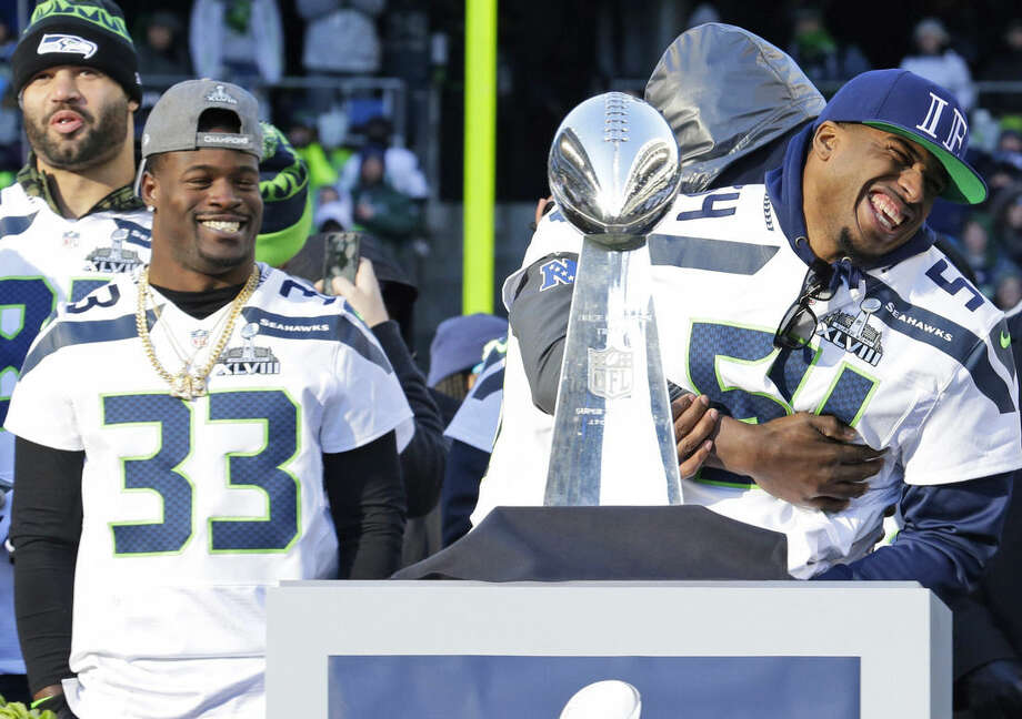 FILE - In this Feb. 5, 2014, file photo, Seattle Seahawks linebacker Bobby Wagner, right, is tackled by teammate Derrick Coleman, after Wagner jumped into the TV camera shot while Seahawks coach Pete Carroll was speaking to the crowd at a rally at CenturyLink Field in Seattle. At left is Christine Michael (33). The Seahawks draft class of 2012 will reminisce about the way pundits gave them failing grades. The group that was ridiculed and included Russell Wilson, All-Pro Bobby Wagner and linebacker Bruce Irvin is about to play in its second straight NFC championship game. (AP Photo/Ted S. Warren, File)