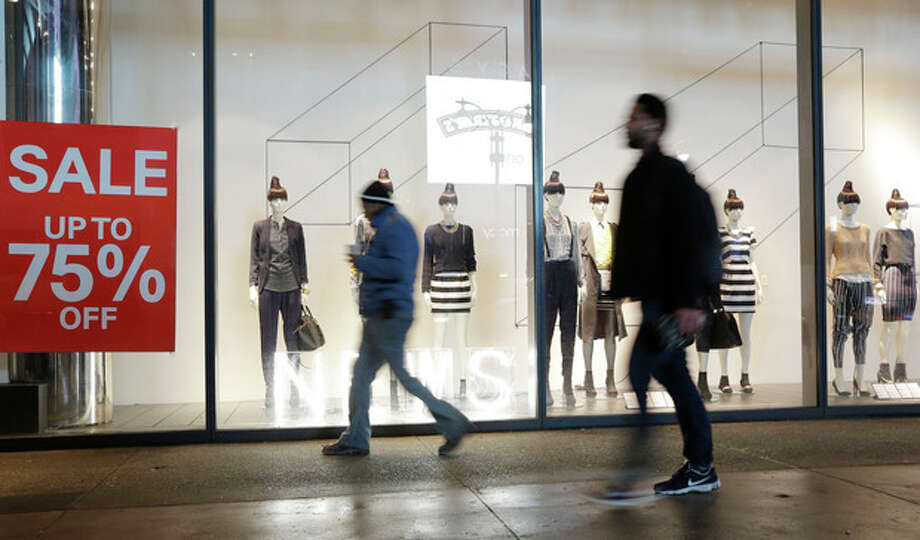 Pedestrians pass an H&M storefront window advertising discounts up to 75%, Tuesday, Jan. 14, 2014 in New York. Americans bought more clothing in December, clicked frequently at online retailers and paid higher gas prices. They cut back on cars and almost everywhere else, providing a lackluster end to the holiday shopping season. Retail sales rose just 0.2 percent last month, the Commerce Department said Tuesday. (AP Photo/Mark Lennihan) / AP
