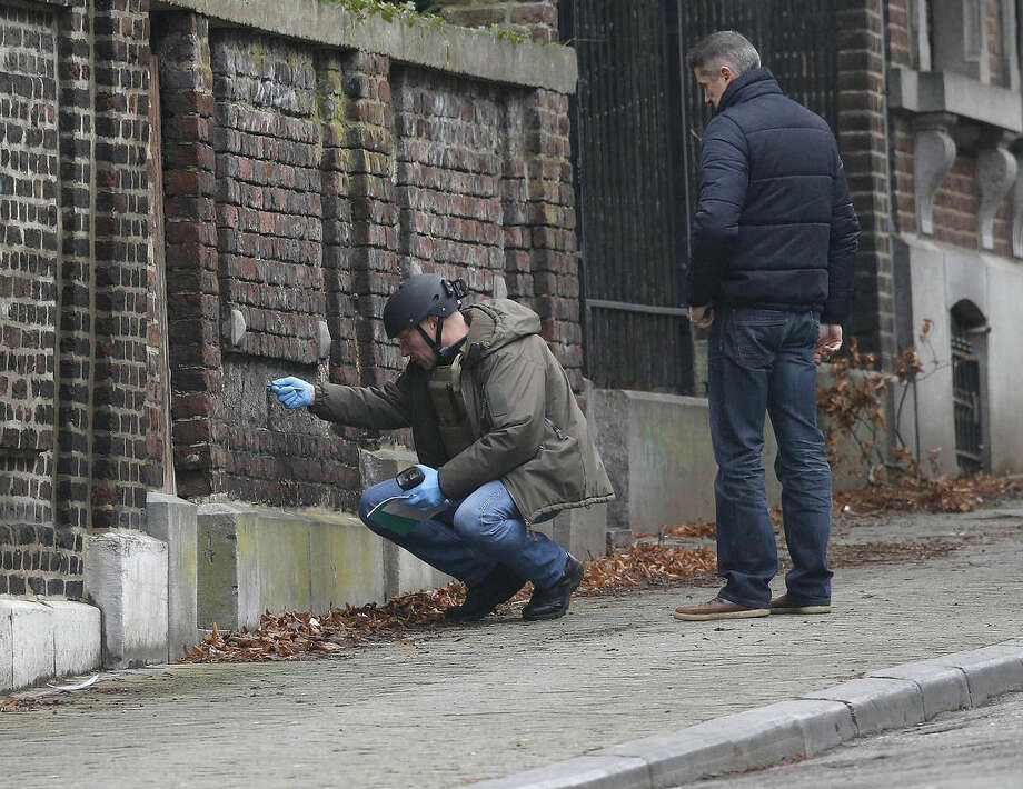 Belgian police officers examine a wall in a street in Verviers, Belgium, Friday, Jan. 16, 2015. The street was blocked after security forces took part in anti-terrorist raids in Verviers, eastern Belgium on Thursday in which two people were killed and one arrested during a shootout in an anti-terrorist operation in the eastern city of Verviers. (AP Photo/Frank Augstein)