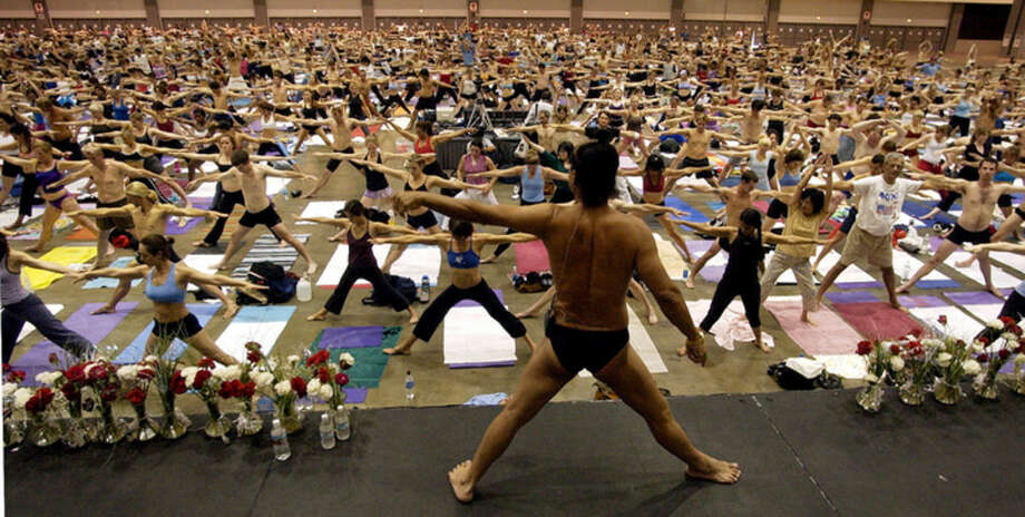 FILE - In this Sept. 27, 2003, file photo, Bikram Choudhury, front, founder of the Yoga College of India and creator and producer of Yoga Expo 2003, leads what organizers hope will be the world's largest yoga class at the Los Angeles Convention Center. A Los Angeles jury on Monday, Jan. 25, 2016, ordered Choudhury to pay more than $900,000 in compensatory damages after finding he had subjected a lawyer to harassment and retaliation. (AP Photo/Reed Saxon, File)