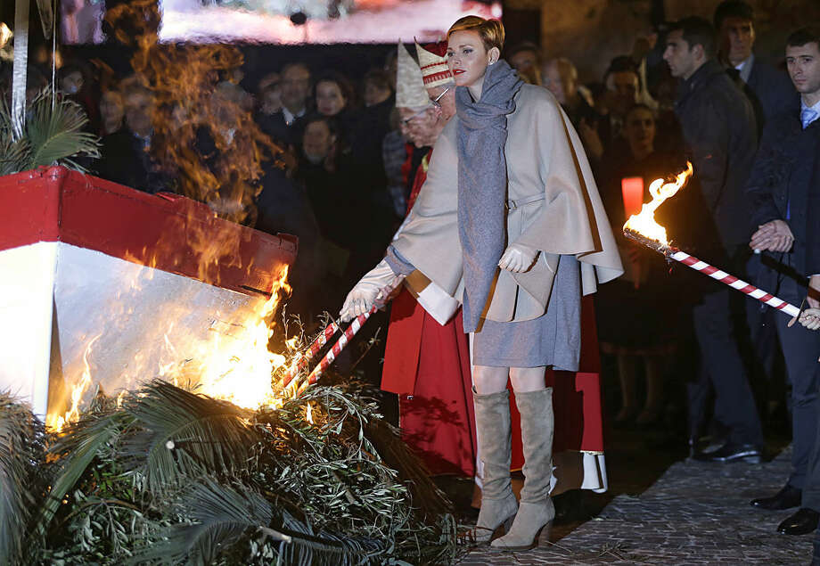Prince Albert II of Monaco's wife Princess Charlene sets fire to a fishing boat during the St. Devote festivities, Tuesday, Jan. 26, 2016, in Monaco. Saint Devote is the patron saint of the Grimaldi family, reigning in Monaco, and every Jan. 27th, the Principality celebrates St. Devote's Day as a national holiday. (AP Photo/Lionel Cironneau)