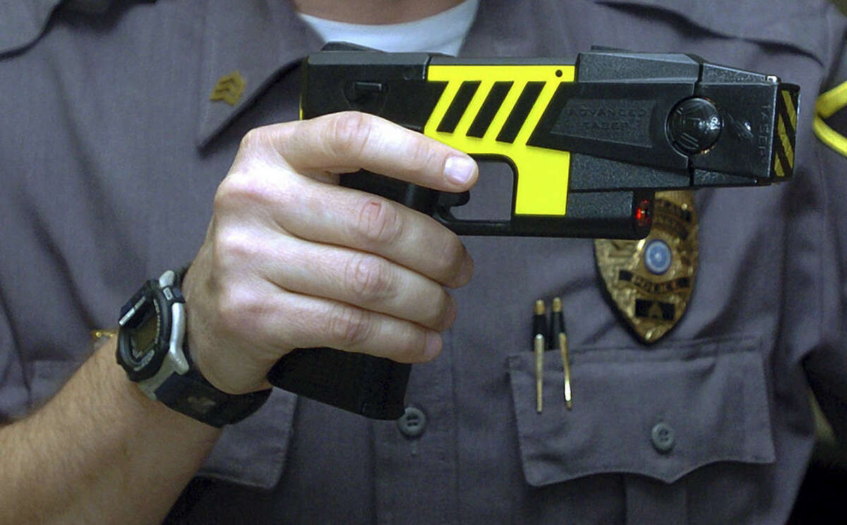 FILE - In this Oct. 28, 2004 file photo, an officer holds a stun gun used by his police department in a Farmington, Conn. Police across Connecticut disproportionately fired stun guns at blacks and Hispanics in 2015 while whites were the main beneficiaries when officers only threatened to use the weapons, according to preliminary data from the nation's first accounting by a state of law enforcement stun gun use. State officials cautioned against making quick conclusions about the figures, saying they have just begun to analyze them after the Jan. 15, 2016 deadline for police departments to submit the reports. Civil liberties advocates also said the data appear to show racial disparities on the surface, but more analysis is needed. (AP Photo/Bob Child, File)