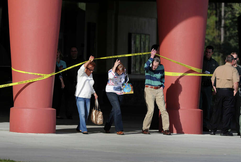 Patrons leave Cobb theater after a shooting Monday, Jan. 13, 2014, in Wesley Chapel, Fla. Authorities say a retired Tampa police officer has been charged with fatally shooting a man during an argument over cellphone use at the theater. (AP Photo/The Tampa Tribune, Cliff Mcbride) / The Tampa Tribune