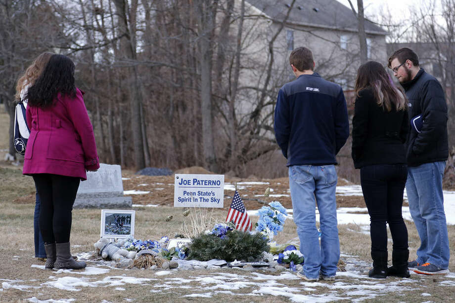A group of Penn State students gather around the grave of the late Penn State football coach Joe Paterno, Friday, Jan. 16, 2015 in State College, Pa. The NCAA announced a settlement Friday with Penn State that will give the school back 112 wins wiped out during the Jerry Sandusky child molestation scandal and restore Paterno as the winningest coach (409) in major college football history. (AP Photo/Gene J. Puskar)