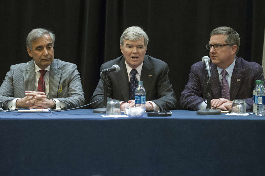 Division 1 board of directors members Harris Pastides, left, University of South Carolina and Kirk Schulz, right, Kansas State University president, listen as NCAA President Mark Emmert speaks with reporters during a news conference at the NCAA Convention in Oxon Hill, Md., Friday, Jan. 16, 2015. The NCAA announced Friday, a settlement with Penn State that will give the school back 112 wins wiped out during the Jerry Sandusky child molestation scandal and restore the late Joe Paterno as the winningest coach in major college football history. (AP Photo/Cliff Owen)