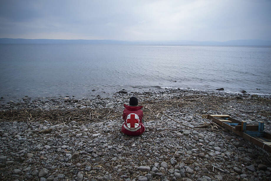 A member of the Greek Red Cross waits for migrants and refugees to arrive on a beach of the Greek island of Lesbos Tuesday, Jan. 26, 2016. More than 850,000 people, most fleeing conflict in Syria and Afghanistan, entered Greece by sea in 2015, according to the UNHCR, and already in 2016, some 35,455 people have arrived despite plunging winter temperatures.(AP Photo/Mstyslav Chernov)