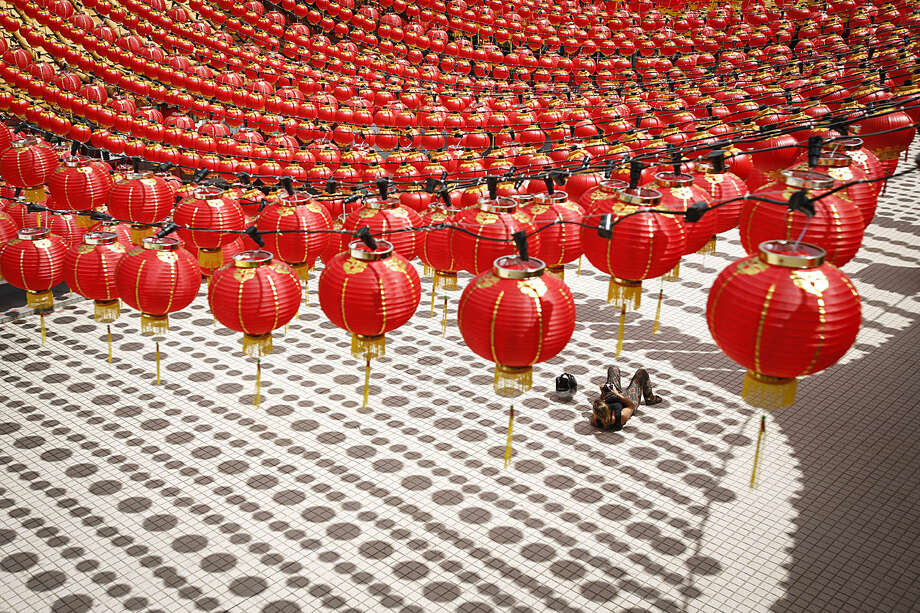 A tourist lies on the floor cast with shadows of traditional Chinese lanterns ahead of the Lunar New Year celebrations in Kuala Lumpur, Malaysia, Wednesday, Jan. 27, 2016. The Lunar New Year which falls on Feb. 8 this year marks the Year of the Monkey in the Chinese calendar. (AP Photo/Joshua Paul)