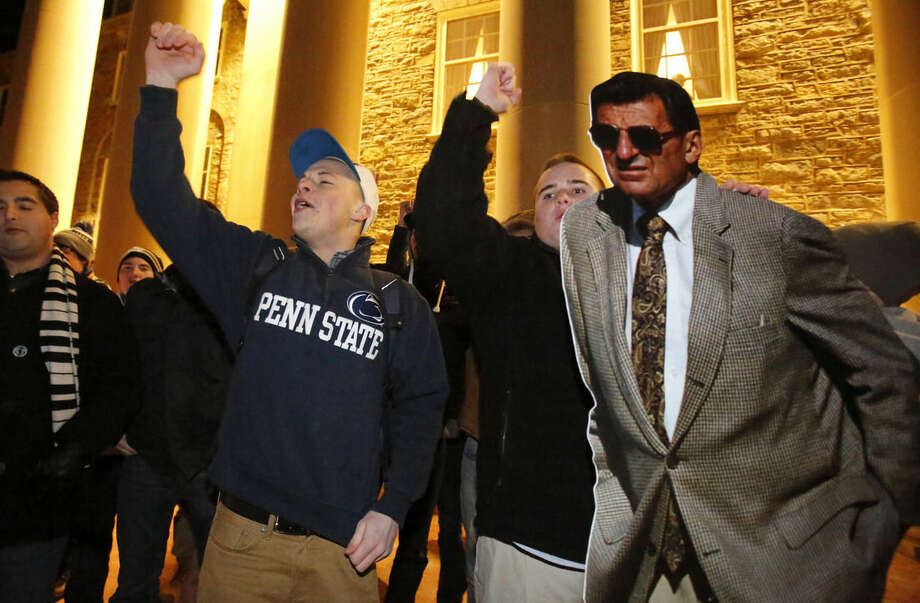 A group of Penn State students gather with a cardboard cutout of the late Penn State head football coach Joe Paterno outside Old Main on campus to celebrate the reversal of NCAA sanctions against the Penn State football program Friday, Jan. 16, 2015 in State College, Pa.. The NCAA has restored 112 of late head coach Joe Paterno's 409 career wins, reinstating Paterno as the winningest coach in major college football history. (AP Photo/Gene J. Puskar)