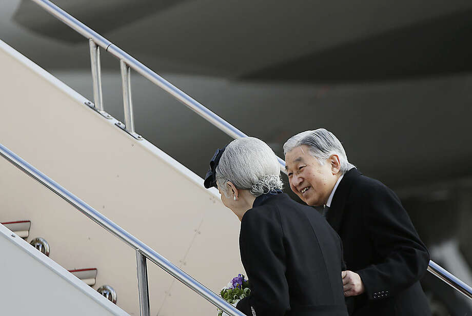 Japan's Emperor Akihito smiles at Empress Michiko as they board their airplane to leave for the Philippines at Haneda International Airport in Tokyo, Tuesday, Jan. 26, 2016. Akihito and Michiko left for a trip to the Philippines that suffered under Japanese occupation during World War II. (AP Photo/Eugene Hoshiko)