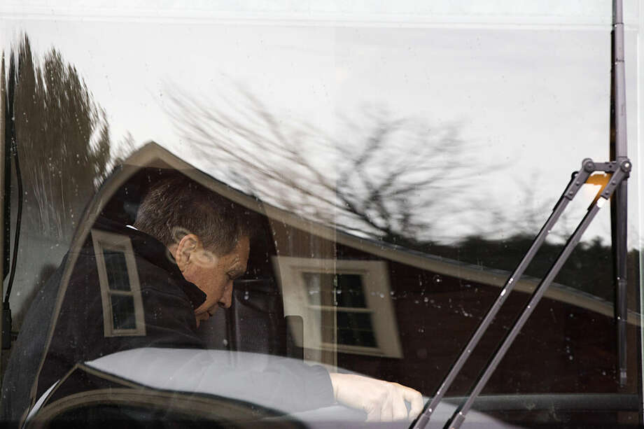 Trees, the sky, and a building is reflected in his bus window as Republican presidential candidate, Ohio Gov. John Kasich steps onto his bus after a campaign stop, Tuesday, Jan. 26, 2016, in New Boston, N.H. (AP Photo/Matt Rourke)