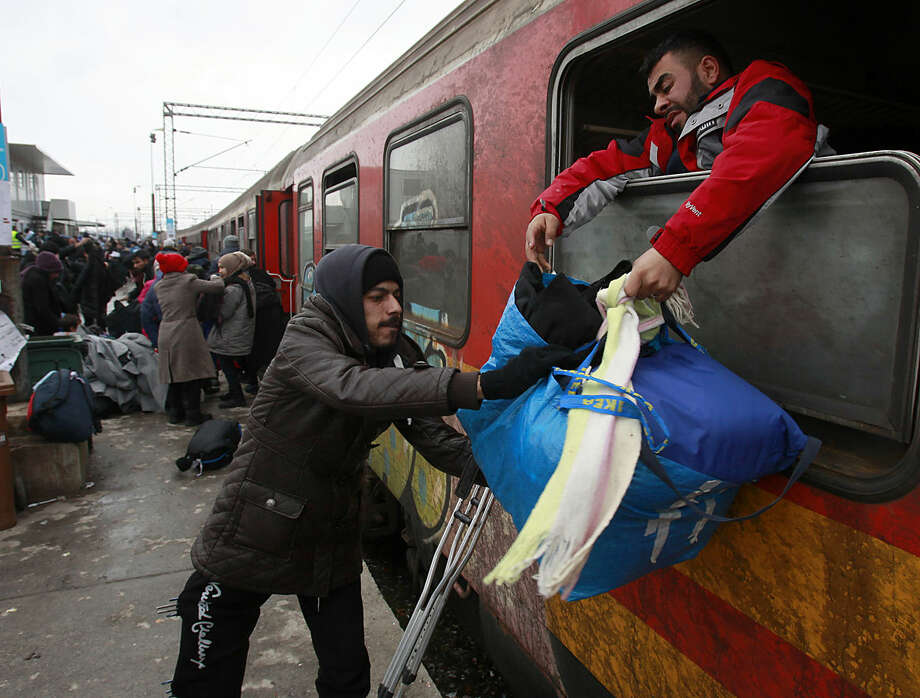 """Refugees disembark from a train as they arrive to the transit center for refugees near northern Macedonian village of Tabanovce, before continuing their journey to Serbia, Tuesday, Jan. 26, 2016. European Union member states """"gave a clear signal"""" that if they can't stop the migrants reaching Greece, they would consider helping Greece's neighbor Macedonia to better seal its border to slow the movement of migrants into other European countries, said Monday Dutch State Secretary Klaas Dijkhoff. (AP Photo/Boris Grdanoski)"""