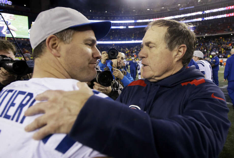 FILE - In this Jan. 11, 2014, file photo, New England Patriots head coach Bill Belichick, right, hugs Indianapolis Colts and former Patriots kicker Adam Vinatieri after an AFC divisional NFL playoff football game in Foxborough, Mass. Vintaieri left New England with three Super Bowl rings. Since joining the Colts, he's added another one. He returns to his old stomping grounds for perhaps his final game at New England. (AP Photo/Stephan Savoia, File)
