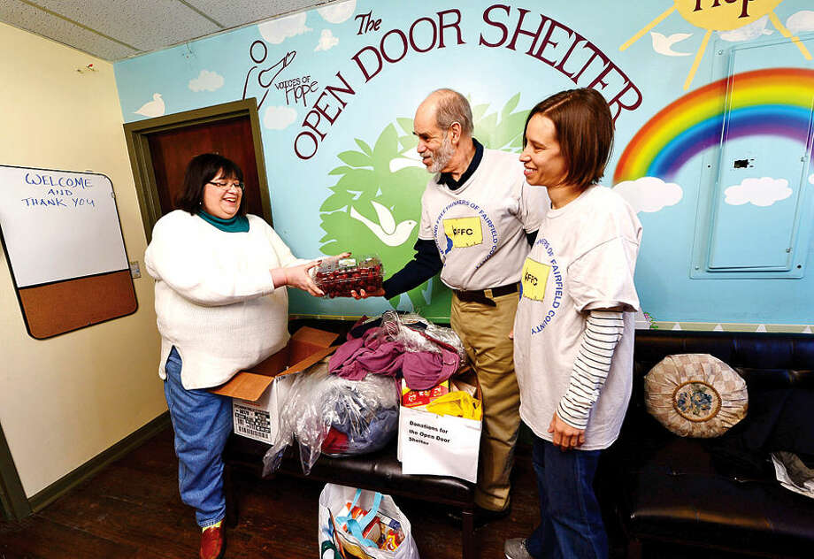 Hour photo / Erik Trautmann One at Open Door Shelter Executive Director Jeanette Archer-Simons receives a donation from Cary and Jocelyn Shaw of The Humanists and Freethinkers of Fairfield County (HFFC). The HFFC seeks to promote Humanism and free thought in our community.