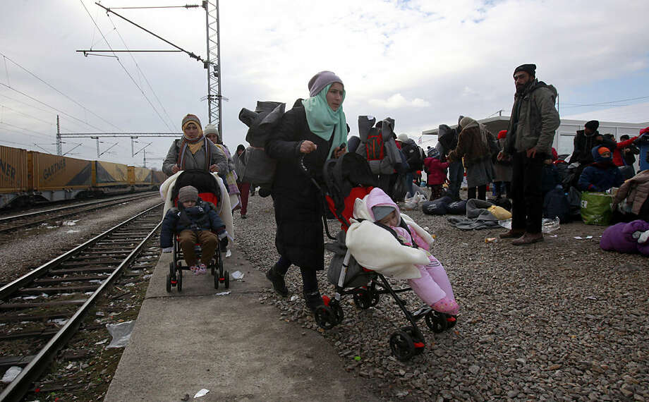 "Refugees push their children in strollers as they continue their journey to Serbia from the transit center for refugees near northern Macedonian village of Tabanovce, Tuesday, Jan. 26, 2016. European Union nations took a step Monday toward isolating Greece amid acrimony over Athens' failure to stem the flow of migrants at its Mediterranean island borders. The member states ""gave a clear signal"" that if they can't stop the migrants reaching Greece, they would consider helping Greece's neighbor Macedonia to better seal its border to slow the movement of migrants into other European countries. (AP Photo/Boris Grdanoski)"
