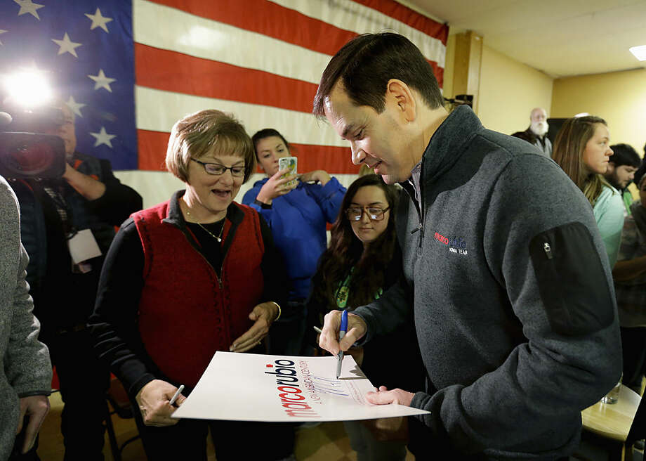 Republican presidential candidate, Sen. Marco Rubio, R-Fla. signs a campaign poster after a campaign event at American Legion Post 34, Tuesday, Jan. 26, 2016 in Oskaloosa, Iowa. (AP Photo/Chris Carlson)