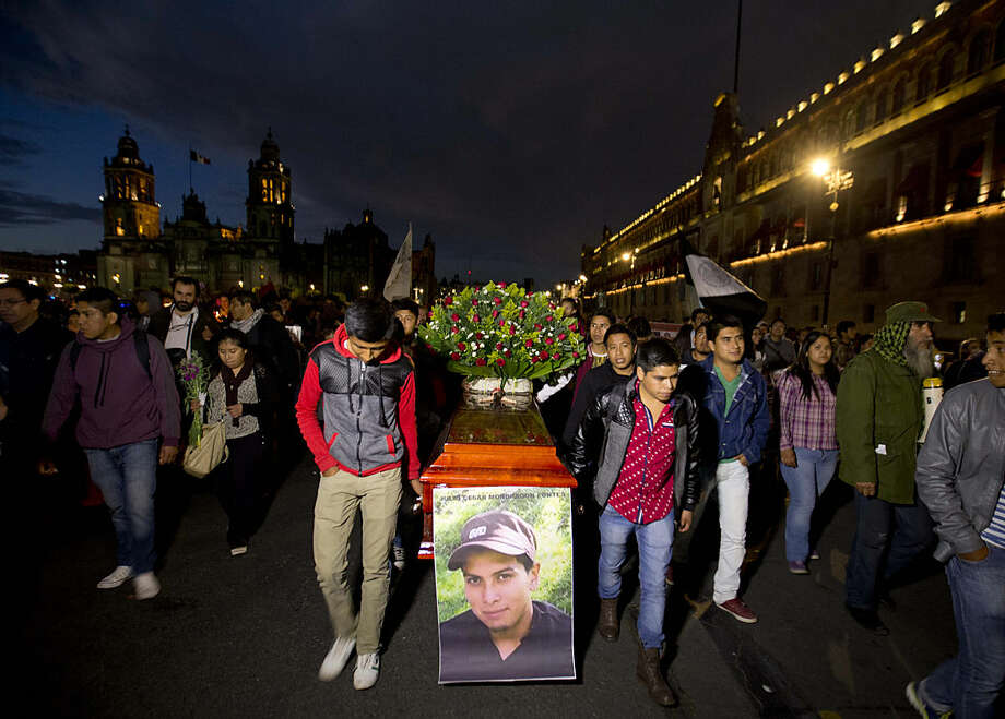 Protestors carry an empty coffin with the image of Julio Cesar Mondragon, who was killed in September 2014 on the same night 43 of his fellow students from a rural teachers college disappeared in the southern state of Guerrero, during a march marking the 16-month anniversary of their disappearance, in Mexico City, Tuesday, Jan. 26, 2016. Mondragon family lawyer Sayuri Herrera is questioning the detention of a man accused killing the Julio Cesar. (AP Photo/Eduardo Verdugo)