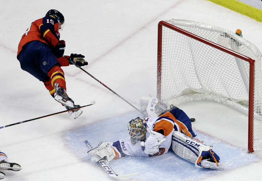 Florida Panthers' Scottie Upshall (19) scores a goal against New York Islanders goalie Kevin Poulin during the second period of an NHL hockey game, Tuesday, Jan. 14, 2014, in Sunrise, Fla. (AP Photo/Lynne Sladky) / AP