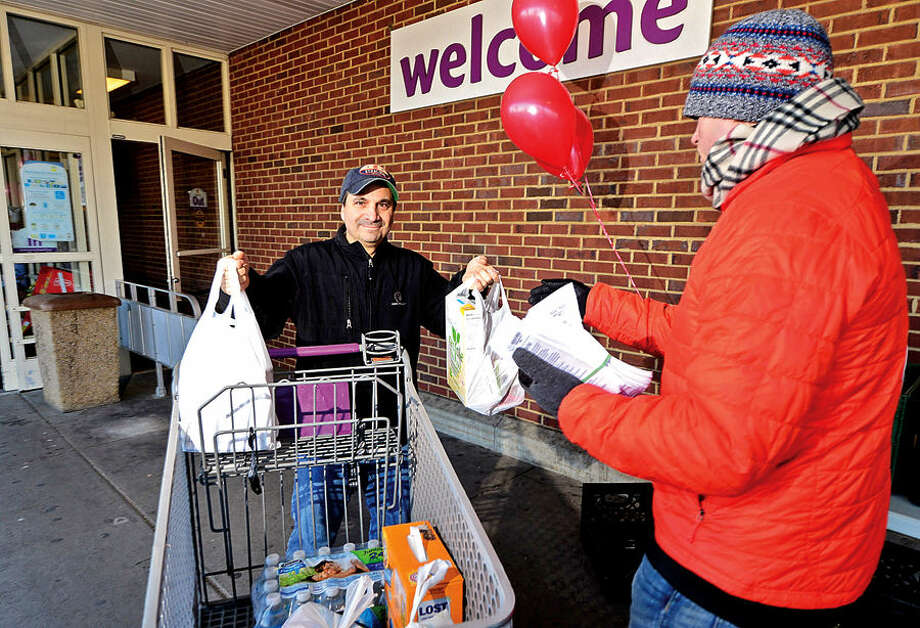 Hour photo / Erik Trautmann Person-to-Person volunteer Chris Maduri, right, solicit donations of food for the needy from local resident including Doug Raymond at Super Stop and Shop on CT Ave Saturday. Person-to-Person is a volunteer driven, community supported agency which, through the sharing of goods and talents, responds to individuals and families who lack the basic necessities or resources to improve their lives.