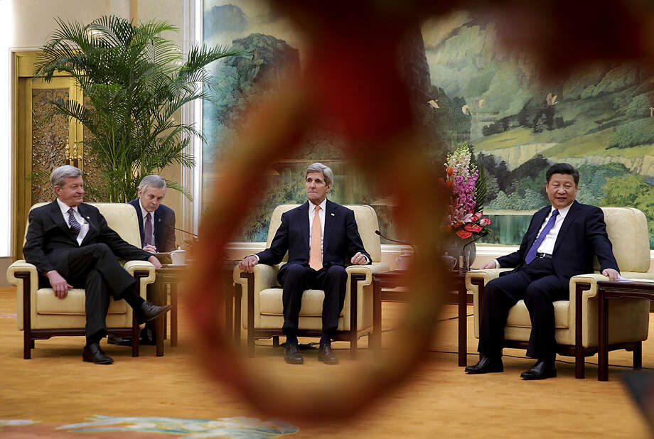 U.S. Secretary of State John Kerry, center, is seen through a loop of a rope used as a security line for the media as he and U.S. Ambassador to China Max Baucus, left, meet with Chinese President Xi Jinping at the Great Hall of the People in Beijing, Wednesday, Jan. 27, 2016. (AP Photo/Andy Wong, Pool)