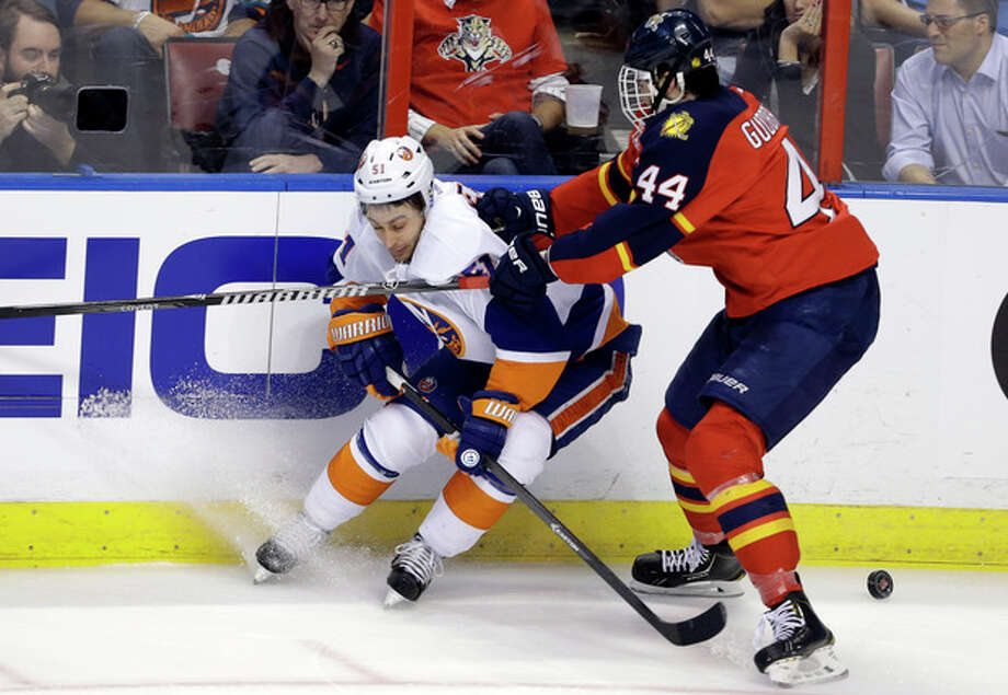 New York Islanders' Frans Nielsen (51) and Florida Panthers' Erik Gudbranson (44) go for the puck during the first period of an NHL hockey game, Tuesday, Jan. 14, 2014, in Sunrise, Fla. (AP Photo/Lynne Sladky) / AP