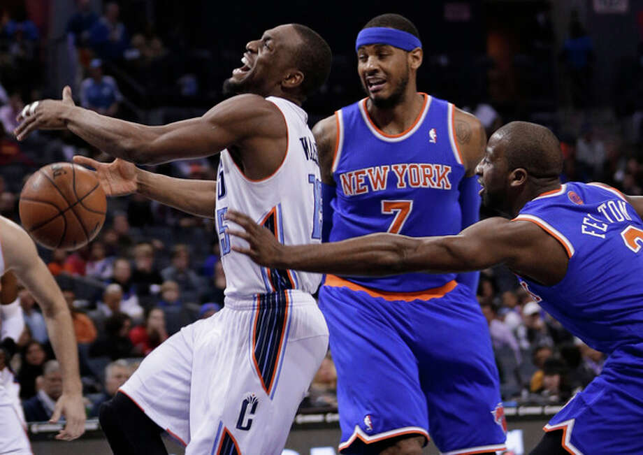Charlotte Bobcats' Kemba Walker, left, is fouled as he drives past New York Knicks' Carmelo Anthony, center, and Raymond Felton, right, during the first half of an NBA basketball game in Charlotte, N.C., Tuesday, Jan. 14, 2014. (AP Photo/Chuck Burton) / AP